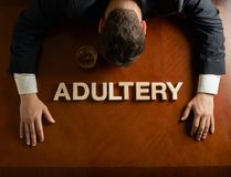 Word Adultery and devastated man composition. Word Adultery made of wooden block letters and devastated middle aged caucasian man in a black suit sitting at the royalty free stock photos