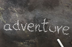The word ADVENTURE written with chalk on black stone. Royalty Free Stock Photography