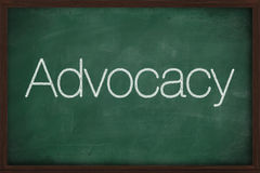 The word Advocacy handwritten. With white chalk on a blackboard Stock Photography