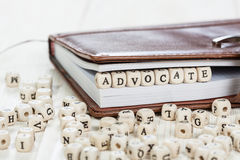 Word ADVOCATE on old wooden table. Word ADVOCATE written on a wooden block in a book. On old wooden table Stock Image
