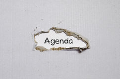 The word agenda appearing behind torn paper Stock Image