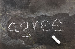 The word agree written with chalk on black stone. Stock Images