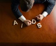 Word AIDS and devastated man composition. Word AIDS made of wooden block letters and devastated middle aged caucasian man in a black suit sitting at the table stock image