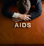 Word AIDS and devastated man composition Royalty Free Stock Photos