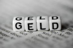 Word allemand GELD a formé par les blocs en bois d'alphabet sur le journal images stock
