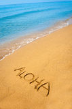 Word Aloha written in sandy on tropical beach. Word Aloha written in sandy on a tropical beach Royalty Free Stock Images