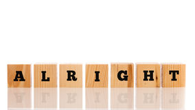 The word - Alright - on wooden blocks. Alright on wooden cubes arranged in a line on a reflective white surface with copyspace above stock photos