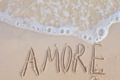Word Amore written on send at seaside Royalty Free Stock Photography