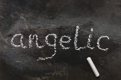 The word angelic written with chalk on black stone. Royalty Free Stock Image
