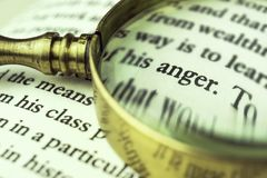 The word `anger` emphasized by a magnifying glass. The word `anger` emphasized by a magnifying glass and wrapped with blurry text Royalty Free Stock Photo