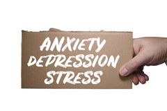 Word Anxiety, Depression and Stress written on cardboard. Clipping path. Hand holding a cardboard label with the word Anxiety, Depression and Stress. Clipping royalty free stock image