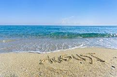 Word AOÛT écrit dans le sable humide Images libres de droits