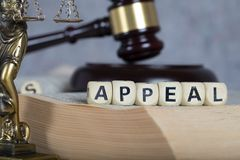 Word APPEAL composed of wooden letters. Statue of Themis and judge's gavel in the background stock image