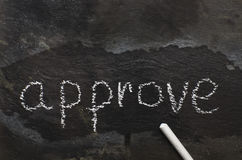The word approve written with chalk on black stone. Stock Image