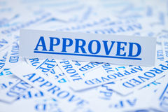 The word approved. The word approved surrounded by some shredded papers Stock Photo