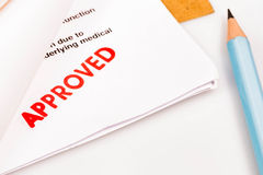 Word Approved on Paper and Pencil. Concept : Word Approved on Paper and Pencil on white background stock photo