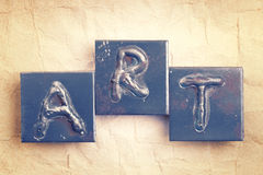 The word ART. Made from metal letters on an old vintage paper background royalty free stock images