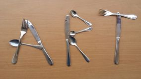 Word Art with metal forks spoons and knifes. The word Art made with metal forks, spoons and knifes royalty free stock photo