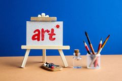 Word Art with red blot on watercolor textured paper. Beautiful wooden easel in art class studio interior, brushes. Pencils in a case, water bottle. Creativity stock images