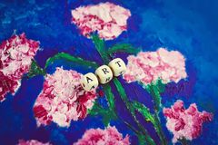 Word art of beads on the picture. Hand drawn carnation flowers on bright blue background. Picture made by oil on cardboard. Word art of wooden beads on the royalty free stock images