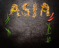Word Asia of asian noodles with chopped chives and red chili on dark slate background, top view Stock Photo