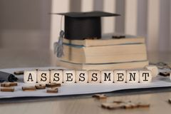 Word ASSESSMENT composed of wooden dices. Black graduate hat and books in the background. Closeup stock photography