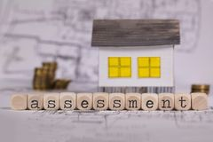 Word ASSESSMENT composed of wooden letter. Small paper house in the background. Closeup royalty free stock photos