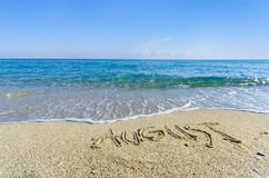 Word AUGUST written in the wet sand Royalty Free Stock Images