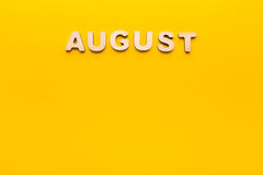 Word August on yellow background Royalty Free Stock Photography
