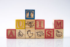 Word AUTISM. Concept of autism word on wooden cubes against white background Royalty Free Stock Photography