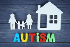 Word AUTISM with family and house. On wooden background Stock Images