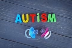 Word AUTISM with pacifiers. On wooden background Stock Images
