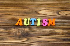 Word `autism` of plastic magnetic letters on wooden background royalty free stock images