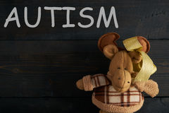 Word AUTISM. And Soft toy moose on wooden texture  background. Copy space Royalty Free Stock Images