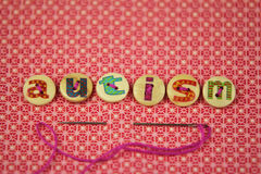 The word autism spelled with buttons with letters on. The word autism spelled with buttons with hand painted letters on, on a vibrant textile background Stock Photo