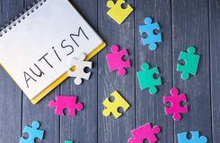 Word AUTISM written in notebook and puzzles. On wooden background Royalty Free Stock Photo
