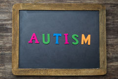 The word autism written on a rustic wooden desk Stock Image