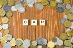 Word AUTO op houten kubus met muntstukkenkader bij houten achtergrond Het concept van financiën stock afbeelding