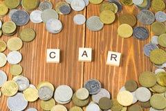 Word AUTO op houten kubus met muntstukkenkader bij houten achtergrond Het concept van financiën royalty-vrije stock foto's