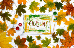 Word autumn, drawn by paints in an album with autumn leaves. Word autumn, drawn by paints in an album on a white background with autumn leaves. Flat lay, top Royalty Free Stock Photography