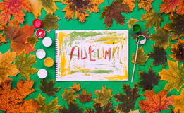 Word autumn, drawn by paints in an album on green background. Word autumn, drawn by paints in an album on a green background with autumn leaves. Flat lay, top Stock Image