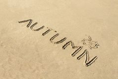 Word autumn handwritten and leaf drawn in sand Royalty Free Stock Photo