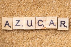 Full frame Word `azucar` on scrabble uppercase letters. Over a brown sugar surface stock photography