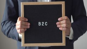 Word B2C from Letters on Text Board in Anonymous Businessman Hands