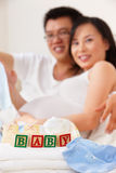 Word baby in front of asian couple Stock Photos