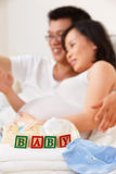Word baby in front of asian couple Stock Photo