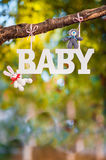 Word Baby and knitting cute toys. White plastic inscription on the branch tree Stock Image