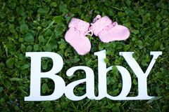 The word `Baby` made of white wooden letters, and pink baby booties, lies on the background of a green grass royalty free stock photo