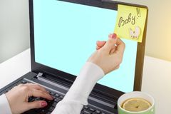 Word baby on a paper sticker stuck on computer from a woman. Laptop, computer woman`s hands background. Stock Image