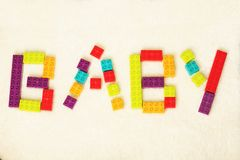 Word of BABY shaped by colorful toy bricks stock photos